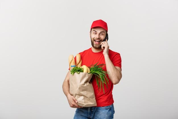 Apuesto hombre de entrega de comestibles hablando con móvil y sosteniendo la bolsa de papel de supermercado.