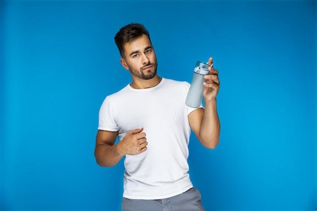 Apuesto hombre europeo en camiseta blanca sobre fondo azul está sosteniendo una botella deportiva en una mano