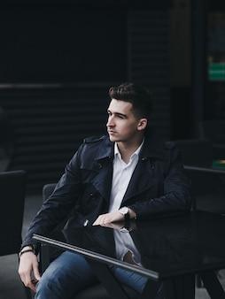 Apuesto hombre exitoso está sentado en una mesa en un restaurante de la calle esperando a un socio comercial