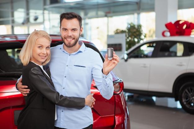 Apuesto hombre feliz abrazando a su encantadora esposa sonriendo a la cámara con la llave del auto en la mano, espacio de copia