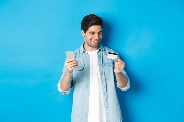 Apuesto hombre feliz pagando algo en línea, con tarjeta de crédito y teléfono móvil, compra en internet, de pie sobre fondo azul.