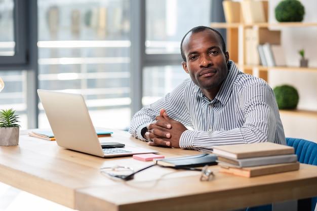Apuesto hombre internacional sentado en su lugar de trabajo mientras va a completar tareas