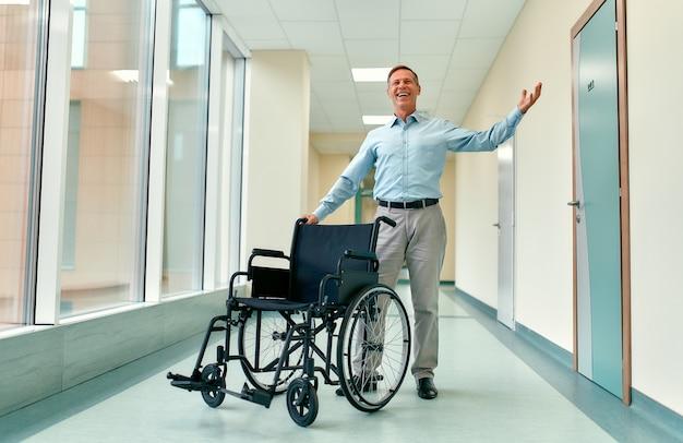 Un apuesto hombre maduro se encuentra recuperado de su discapacidad cerca de una silla de ruedas y alzó la mano en señal de victoria, de pie en el pasillo de la clínica.