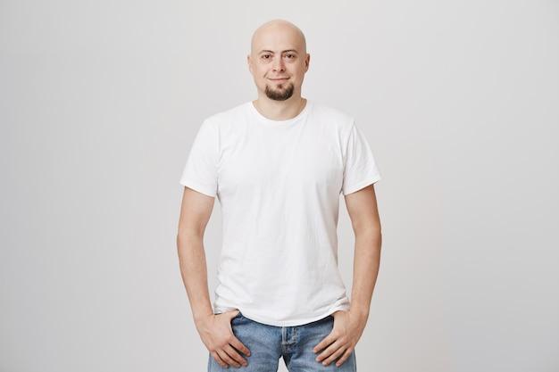 Apuesto hombre de mediana edad calvo con barba vistiendo camiseta blanca casual