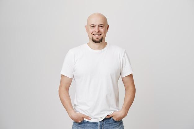 Apuesto hombre de mediana edad calvo sonriente con barba vistiendo camiseta blanca casual