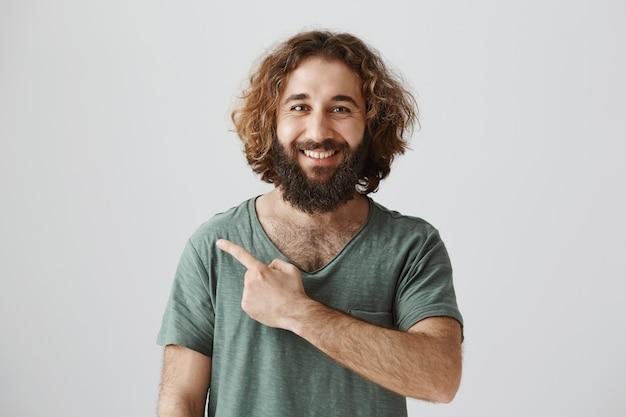Apuesto hombre del medio oriente con barba, sonriendo y señalando con el dedo a la izquierda en el banner