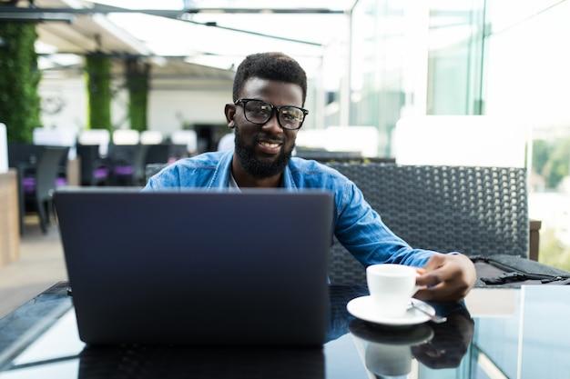 Apuesto hombre de negocios africano con reunión en línea en una computadora portátil en un café y tomando café, panorama, espacio de copia