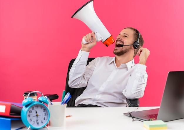 Apuesto hombre de negocios en camisa blanca y auriculares con un micrófono gritando al megáfono apretando el puño loco feliz sentado en la mesa en offise sobre fondo rosa