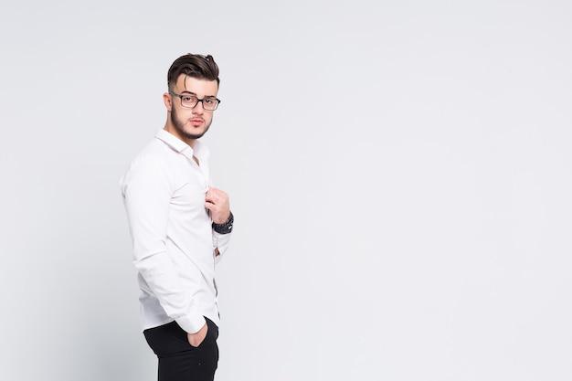 Apuesto hombre de negocios en camisa blanca de pie con los brazos cruzados
