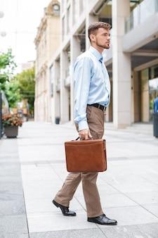 Apuesto hombre de negocios caucásico camina con maletín en la ciudad.
