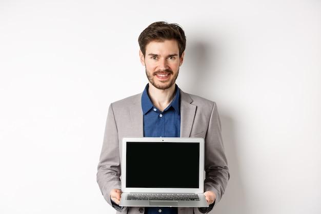 Apuesto hombre de negocios caucásico en traje mostrando la pantalla del portátil vacía, demostrar promo