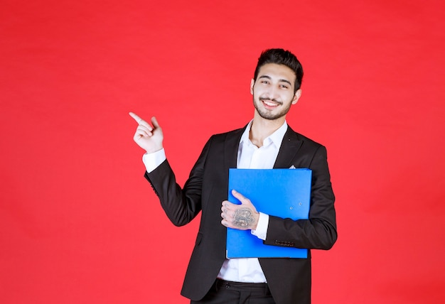 Apuesto hombre de negocios confiado en traje con bloc de notas apuntando a un lado