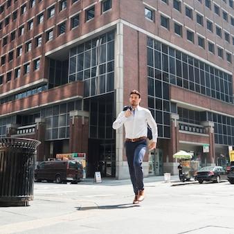 Apuesto hombre de negocios corriendo en la calle