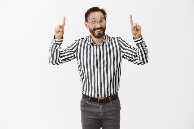 Apuesto hombre de negocios emocionado apuntando con el dedo hacia arriba y sonriendo asombrado