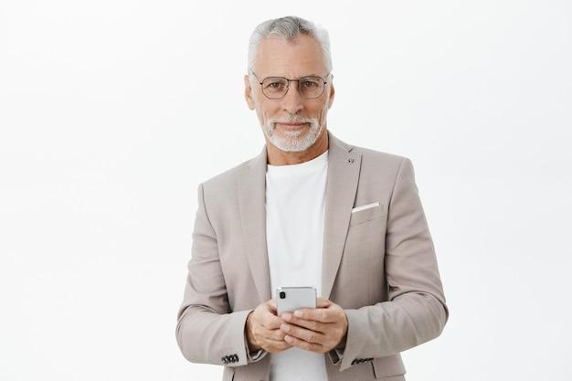 Apuesto hombre de negocios exitoso en traje mediante teléfono móvil