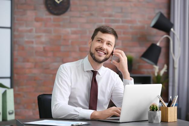 Apuesto hombre de negocios hablando por teléfono móvil mientras trabajaba en la oficina