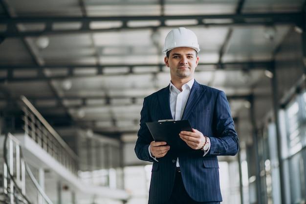 Apuesto hombre de negocios ingeniero en casco en un edificio
