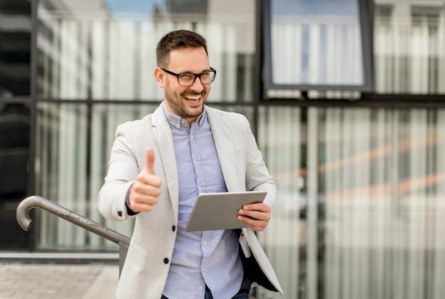 Apuesto hombre de negocios joven con tableta digital por el edificio de oficinas