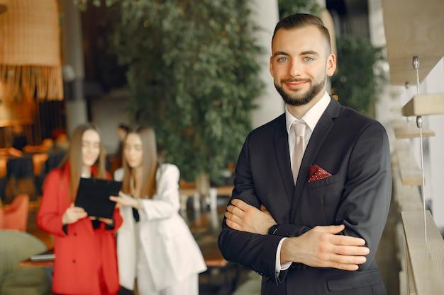 Apuesto hombre de negocios con mujeres de pie y trabajando en un café