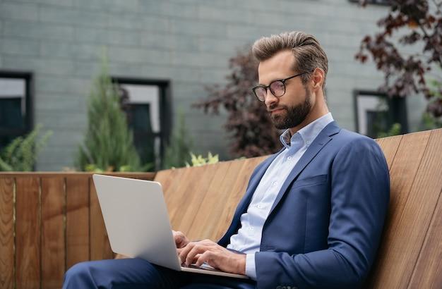 Apuesto hombre de negocios pensativo con ordenador portátil buscando trabajo en línea desde casa