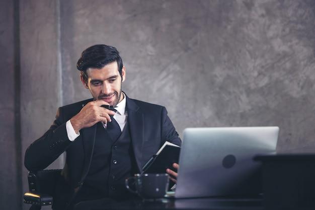 Apuesto hombre de negocios planificando el trabajo y tomando notas.