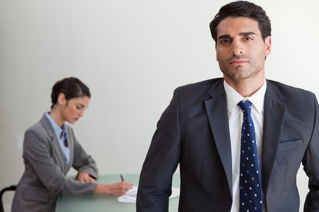 Apuesto hombre de negocios posando mientras su colega está trabajando