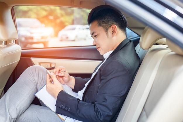 Apuesto hombre de negocios sentado en el asiento trasero del coche y tocando el teléfono