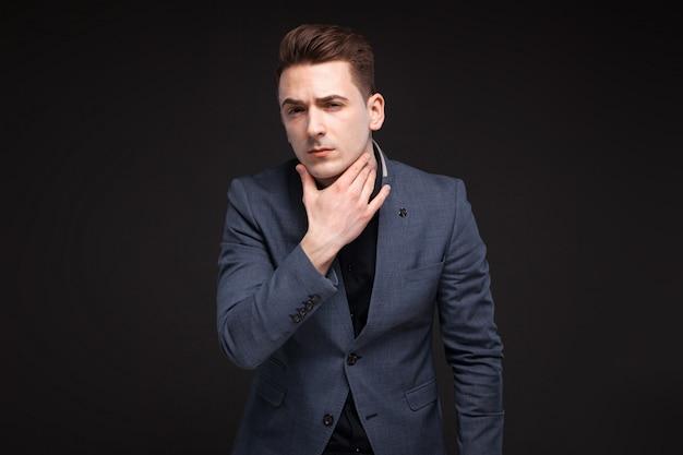 Apuesto hombre de negocios serio en chaqueta gris, reloj costoso y camisa negra