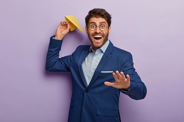 Apuesto hombre de negocios sonriente alegre posando en traje elegante en la oficina