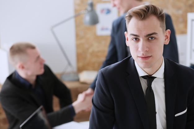Apuesto hombre de negocios sonriente en traje de retrato en el lugar de trabajo