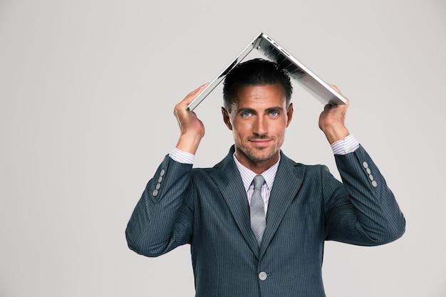 Apuesto hombre de negocios sosteniendo su computadora portátil en la cabeza como techo de casa aislada. mirando a la camara
