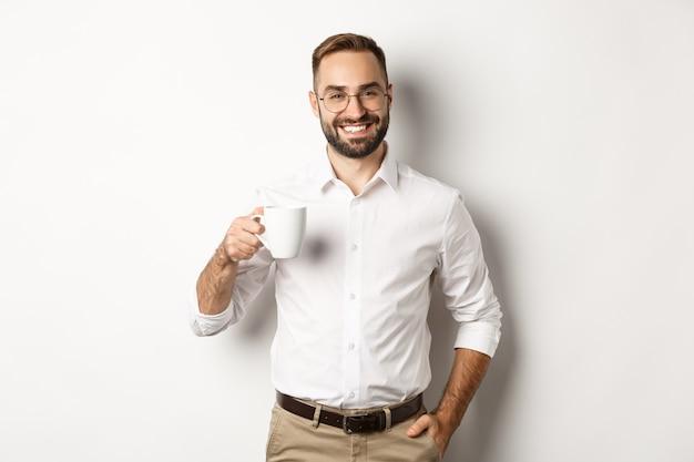 Apuesto hombre de negocios tomando café y sonriendo, de pie contra el fondo blanco.