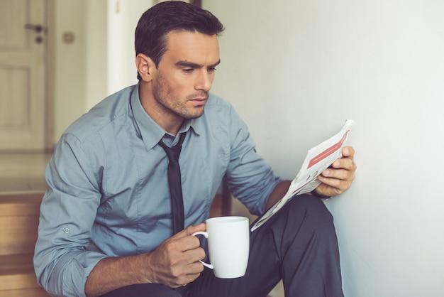 Apuesto hombre de negocios en traje clásico está sosteniendo una taza.