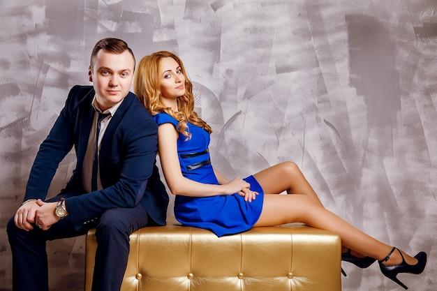Apuesto hombre de negocios en traje posando con hermosa mujer rubia en vestido azul