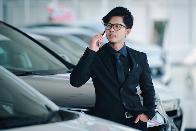 Apuesto hombre de negocios en trajes y gafas hablando por teléfono en la oficina felicitar a las ventas se ha completado para la nueva sala de exposición de automóviles.