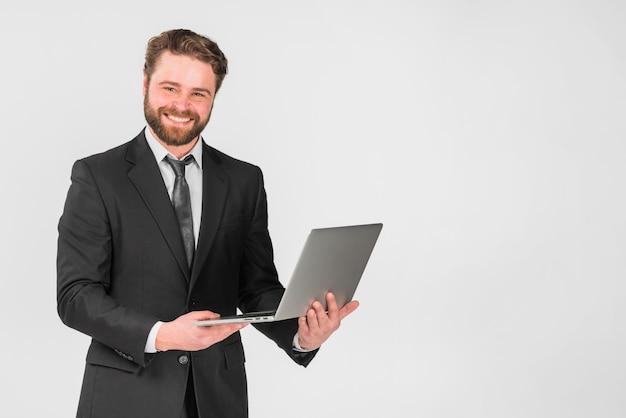 Apuesto hombre de negocios usando laptop y sonriendo