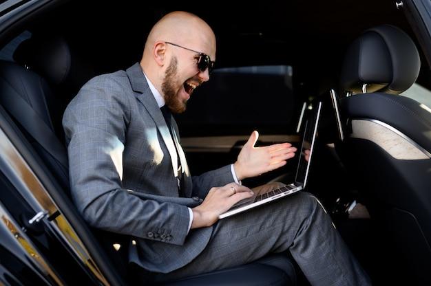 Apuesto hombre de negocios usando su teléfono móvil en un automóvil moderno con un conductor en el centro de la ciudad. concepto de negocio