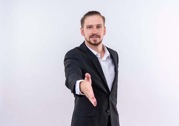 Apuesto hombre de negocios vestido con traje sonriendo amable saludo ofreciendo mano de pie sobre fondo blanco.
