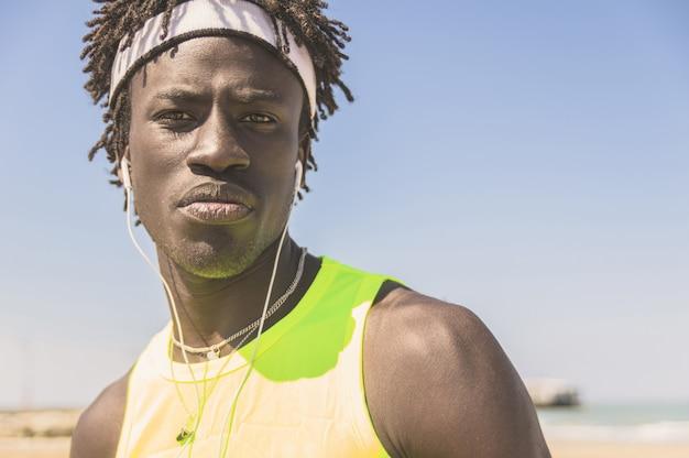 Apuesto hombre negro atlético mirando y escuchando música - concepto sobre deporte y personas