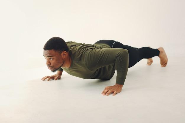 Apuesto hombre negro haciendo yoga en una pared blanca