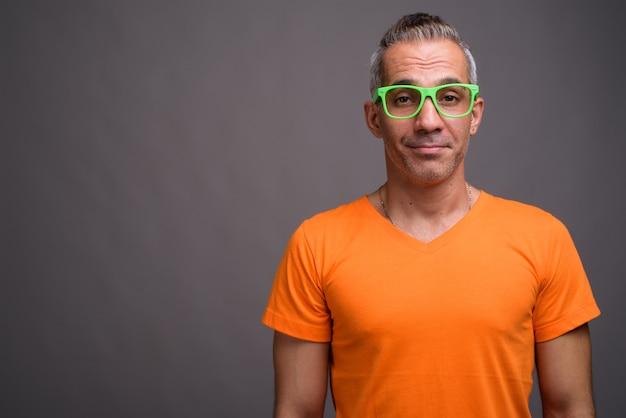 Apuesto hombre persa con cabello gris con camiseta naranja