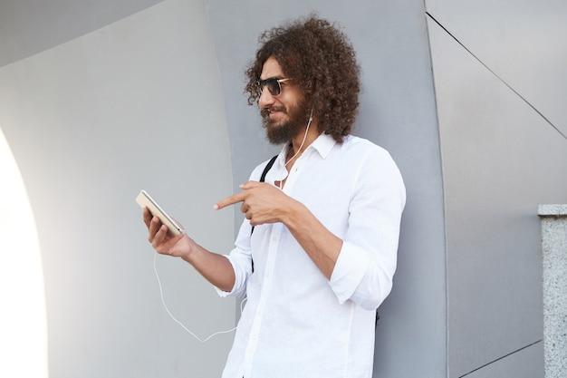 Apuesto hombre rizado joven feliz de pie sobre una pared gris con tableta en mano, con videollamadas con auriculares, gafas de sol y ropa casual