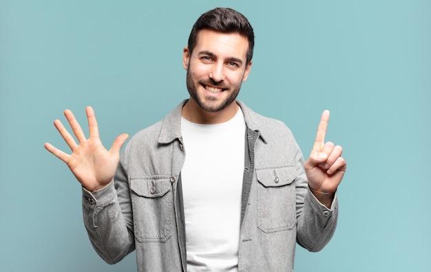 Apuesto hombre rubio adulto sonriendo y mirando amigablemente, mostrando el número seis o sexto con la mano hacia adelante, contando hacia atrás