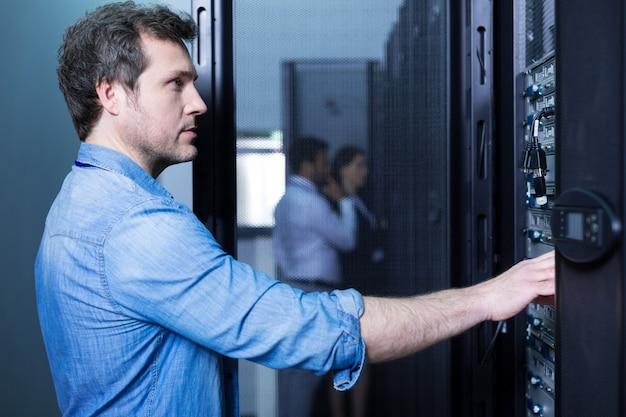 Apuesto hombre seguro inteligente de pie cerca del servidor de comunicaciones y mirándolo mientras hace su trabajo