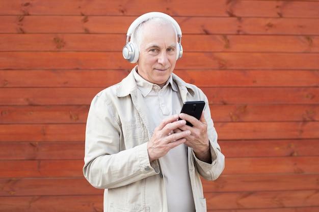 Apuesto hombre senior con auriculares. disfrutando el sonido de la música.