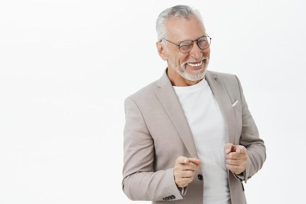 Apuesto hombre senior exitoso en traje señalando con el dedo, sonriendo descarado