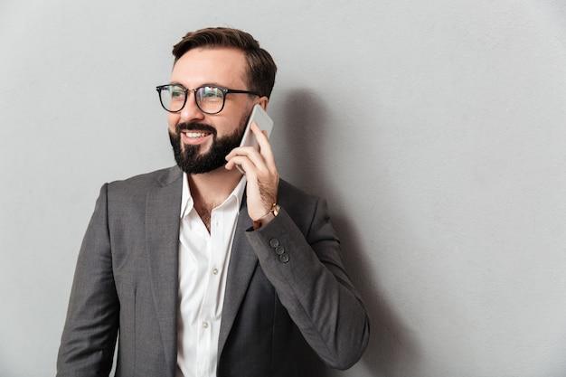 Apuesto hombre serio en ropa formal teniendo conversación móvil con smartphone aislado sobre gris