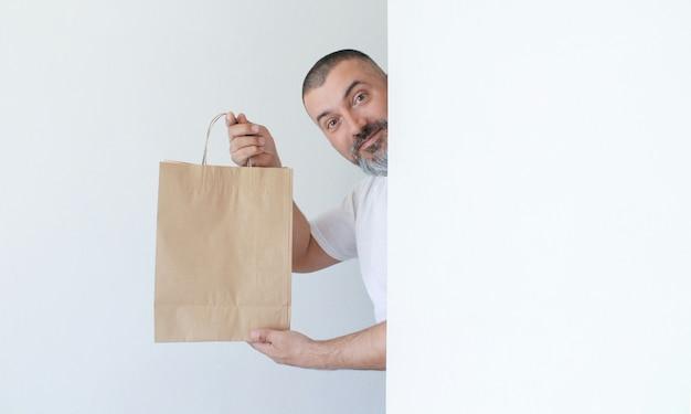 Apuesto hombre sonriente con barba mirando detrás de una pared blanca y sosteniendo una bolsa de papel en manos aisladas sobre fondo blanco.