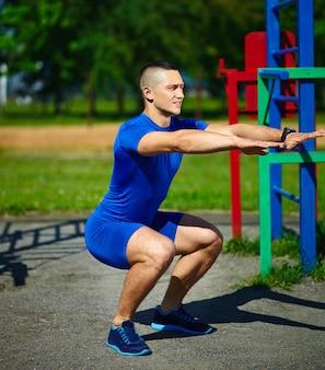 Apuesto hombre srtong saludable hombre masculino haciendo ejercicio en el parque de la ciudad - conceptos de fitness en un hermoso día de verano cerca de la barra horizontal