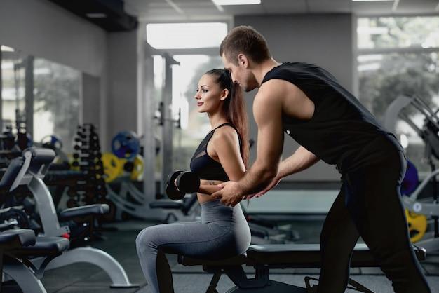 Apuesto instructor personal ayudando a su clienta a entrenar con pesas.